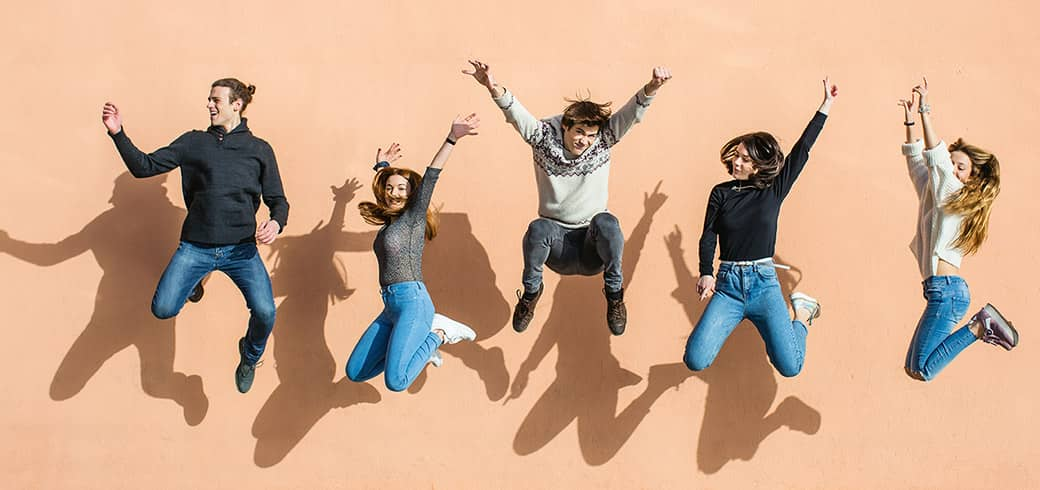 A group of friends jumping with their hands in the air laughing and smiling