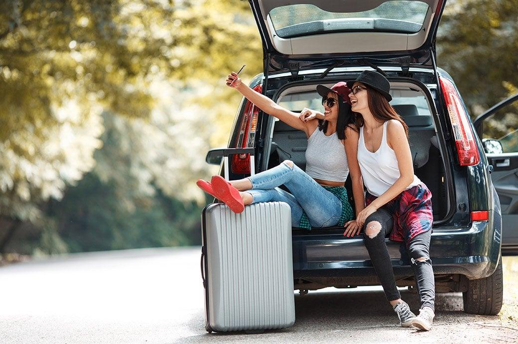 Dos mujeres en un baul de un auto riendose sacandose una selfie